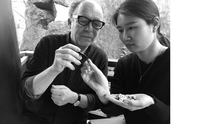 Two jewellery designers, Kim Buck and Zhang Qiao, working on a bead