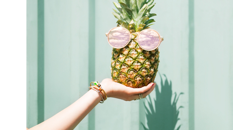 Hand holding pineapple wearing a bracelet