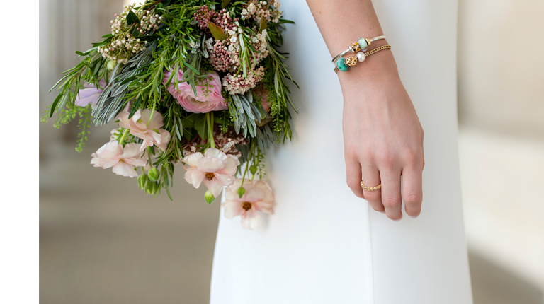 Wedding bouquet and a hand showing Gold foxtail bracelet with emerald gemstone, white pearl and  Blanket of Love, gold bead, and a silver bangle with a glass bead and Hearts Galore, Gold bead, and a Troll ring in 18 karat gold