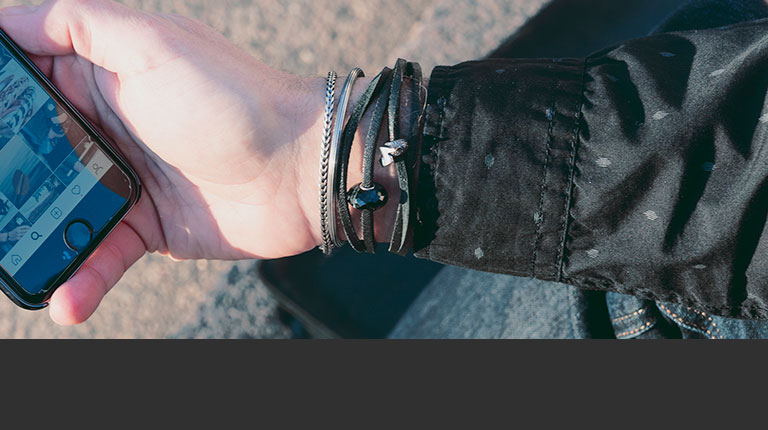 Black leather bracelet and star bangle on male model