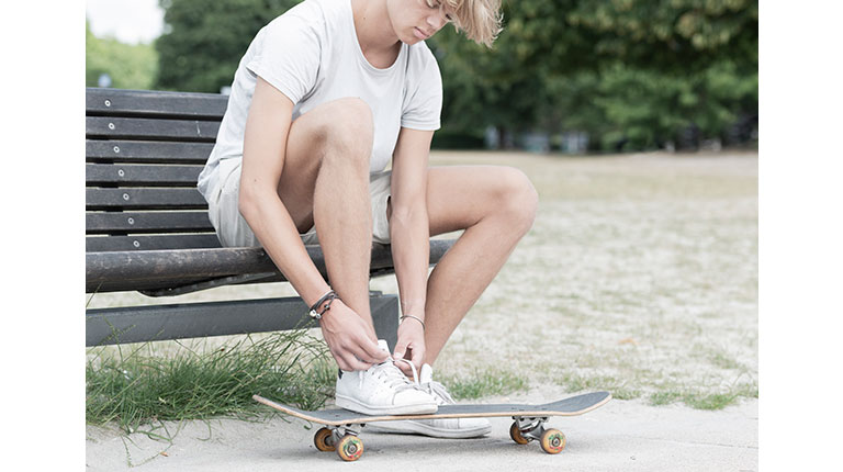 Image of a young man with his skateboard. He is wearing Trollbeads leather bracelets.