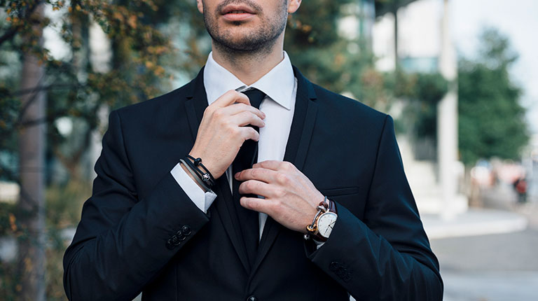 Man in a suit wearing Trollbeads leather bracelet and silver bracelet.