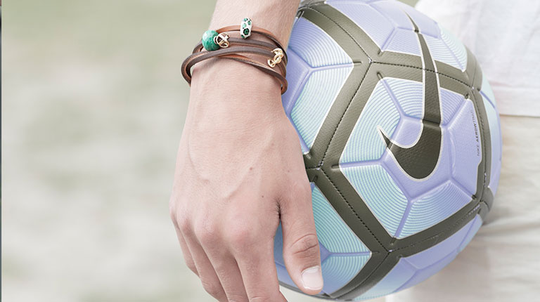 Image of a man holding a soccer ball and wearing a brown Trollbeads leather bracelet.