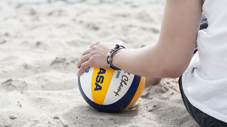 Image of a man's hand on a volley ball. He is wearing a Trollbeads leather bracelet. Taking a break and relaxing on the beach.