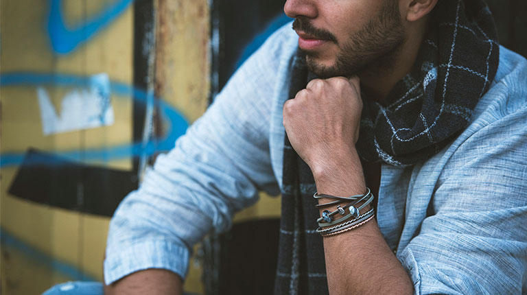 Bohemian man wearing Trollbeads leather bracelets and bangles.
