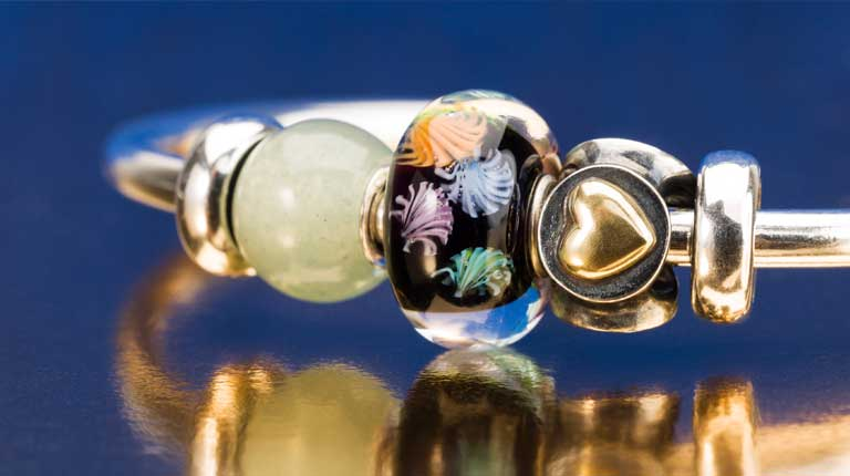 Trollbeads happy new year bead 2020 with the Joy, Peace & Love bead with a gold heart and a petite aventurine bead on a gold plated bangle with gold spacers