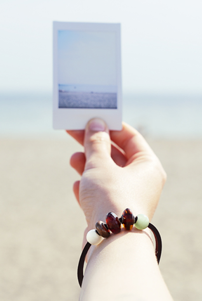Hand holding a poloroid wearing a leather bracelet with amber and petite beads