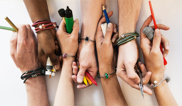 Creative hands wearing trolbeads bracelets holding tools