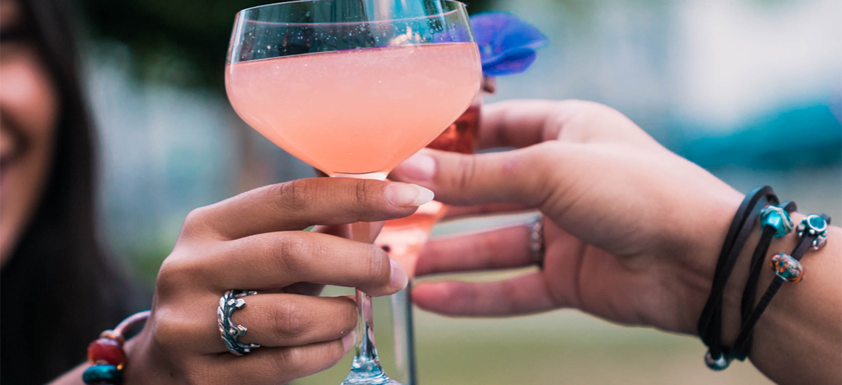 hand holding a pink drink showing a crown ring