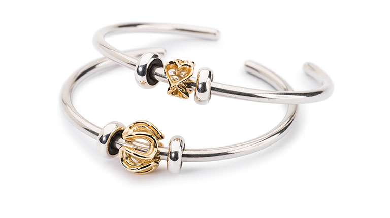L'immagine mostra due bangle Trollbeads con beads in oro.