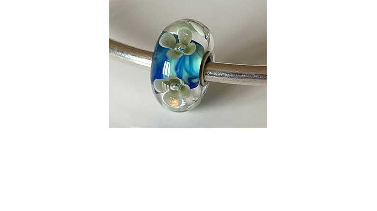 People's Uniques Winner 2020 - a blue, green and gold glitter glass bead with swirling waves.