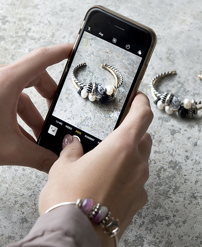 A woman who is wearing a Trollbeads bangle is taking a picture from her phone of another Trollbeads bangle
