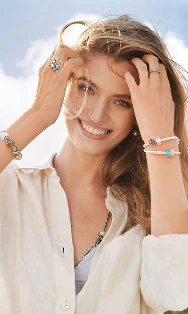 A female model, smiling, standing with her hands in her hair whilst wearing a filled Trollbeads bracelet and ring, all from the brand new Summer 2020 collection.