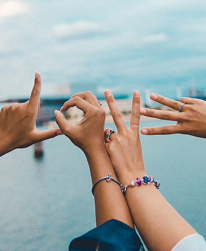Two women wearing Trollbeads jewellery have positioned their hands to spell the word 'LOVE'